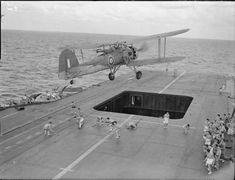 A Fairy Swordfish flies over men playing hockey on the flight deck of an aircraft carrier, WW2