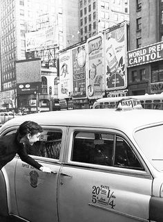 Audrey Hepburn taking a taxi in the middle of Times Square, 1951.