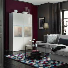 Ein Wohnzimmer mit BESTÅ Vitrine Hochglanz weiß, einem lilafarbenen Sofa mit Récamiere und einem schwarzbraunen Couchtisch