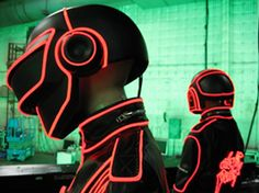 Suits for Daft Punk Alive tour where Enlighted installed several hundred feet of red EL wire on each leather jacket, following the seam lines and key styling details. The Daft Punk logo on the back of each jacket (originally written with metal studs) was re-created with about 300 red LEDs. For the lighted helmets, we attached EL wire to matte black replicas of the metallic helmets that are worn for the earlier part of the show.