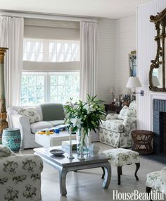"""The living room of this Southampton, New York, house is furnished with family heirlooms. """"Hardly anything is new,"""" says designer Justine Cushing. If something needed reupholstering, she covered it in a classic chintz, Bowood by Colefax & Fowler. The silver-leaf coffee table belonged to a friend, and she likes it because """"it glows."""" She also likes the ethereal quality of white curtains against white walls, painted in Benjamin Moore Aura in Linen White"""