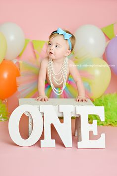 Blog | 11 Sixteen Photography, one letters, white bench, first birthday, girl baby birthday, pink backdrop, pearls, rainbow, tutu, blue headband, balloons,