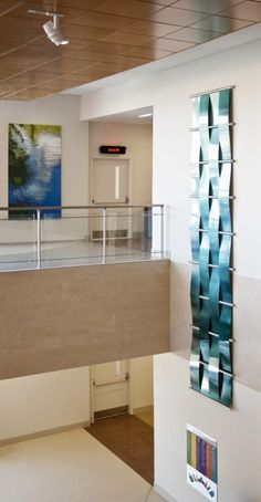 """Two examples of the """"river"""" theme, one a painting depicting a watery reflection and the other a three-dimensional metal sculpture evoking a waterfall. Photo credit: © 2011Skyline Art Services."""