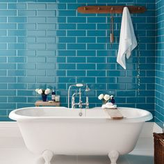 Peacock inspired bathroom wall tile nicely contrasts the tub. Makes a bold statement.