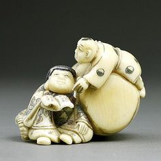 ANTIQUE JAPANESE CARVED IVORY NETSUKE of an man seated and resting on a large barrel and holding a book, while a child hangs on the barrel and appears to be writing on the book being held by the old man. Two signatures, one on the foot of the man, the other in red, by the side of the barrel.
