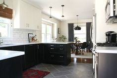 ****modern-meets-traditional black & white kitchen w/ mixed colour upper & lower Ikea cabinets, Corian counter, like the microwave over the stove, china display cab in dining area, would do wood/laminate floor