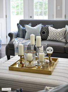 Make a visual statement with a clustered grouping of metal and glass candleholders in varying heights on your coffee table. Large Ottoman Coffee Table, Coffee Table Height, Ottoman Table, Coffee Table Tray, Coffee Table Styling, Decorating Coffee Tables, Coffee Table Design, Table Decor Living Room, Ottoman In Living Room