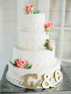 This rose topped wedding cake is simple and pretty. Love the monogram to add a little gold.