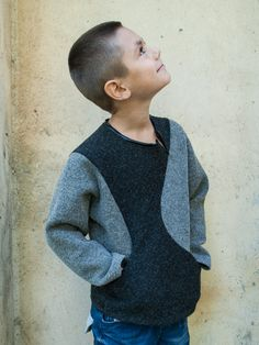 This boys wool cardigan winter sweater is sewn from 2 fabrics - soft black lined wool for front and back panel and wool grey knitted fabric for the sleeves and side panels. Contrast finishing faux leather for neckline and decorative slit. This boys winter blouse has 2 pockets on the front panel, which follow designers cutting shape. The quality soft wool knitted fabric makes it very warm.  Looks good with jeans and other models from our collection.     Your little boy will collect people's…