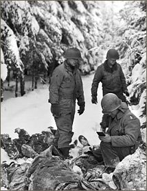 A graves registration officer identifies the American dead among the Germans killed in the Ardennes. January 11, 1945.
