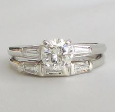PLATINUM Bridal Set! Diamond engagement ring with matching wedding band make up this high quality classic VINTAGE SET! The central stone on this engagement ring is SO fiery, it just sparkles like crazy, photos just do not show its beauty! It is a round brilliant cut that is a fabulous 68pts in size for amazing presence on the hand! To each side are beautiful tapered baguette diamonds, and within the matching wedding band is a central baguette flanked by two tapered baguettes. Crafted from…