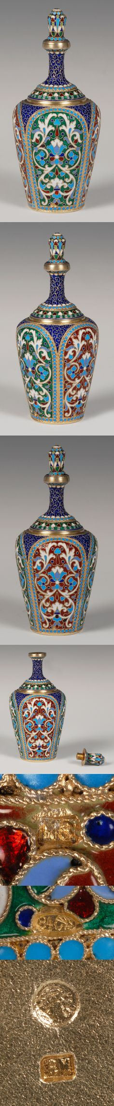 A Russian silver gilt and cloisonne enamel scent bottle, Nikolai Zverev, Moscow, circa 1896-1908. Of oval form with threaded stopper, the bottle decorated with scrolling floral and foliate motifs within a turquoise beaded border against alternating green and red ground panels