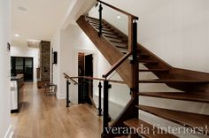 Powder coated iron post, quartersawn oak handrails, and frame-less glass panels. Closed stringer with open hardwood risers.