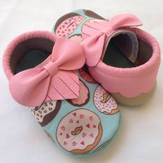 "**Bows not included** Our donut moccs are made of donut printed canvas, baby pink ""frosting' fringe, and an aqua colored suede sole. Great for babies, first walkers, and rough and tumble toddlers. Available with or without a bow. Be sure to add a bow to your cart if you would like your moccs to h..."