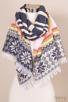 "White and navy woven scarf with stripes and snowflakes pattern. Hot pink, baby pink, and mustard accents. Loose fringe finish. Approx. length 70"" width 22"". 10"