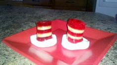 """Cat in the Hat"" jello treats!    1. layer of red jello (large pack w 2cups water)  2. layer of light colored jello (large pack with one cup water and one cup milk)  3. repeat every hour for 5 layers  4. cut jello w fondant or cookie cutter  5. BASE:  one jumbo campfire marshmellow cut into 4 rounds.  (use a wet warm knife for even cuts)  6. allow marshmellow rounds to dry over night so they are not sticky!  7. place jello stacks on marshmellows - you may need a tooth pick to transport"