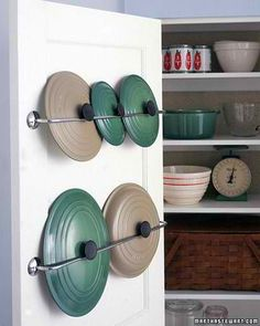 Attach a towel rod to the inside of your cupboard door to hold pot lids - Makes it easy to find the lid that you need, and keeps the cupboard much more organized.