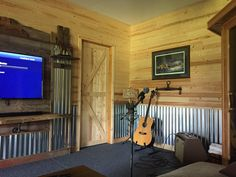 """This had been a regular drywalled room with beige paint. I used Fabral 2 1/2"""" corrugated metal roofing panels from Lowes for the waisncoting and the entertainment center. The wood on the doors and wall are EverTrue 3/8"""" pine planks also from Lowes. I also used weathered barnwood on the entertainment center"""
