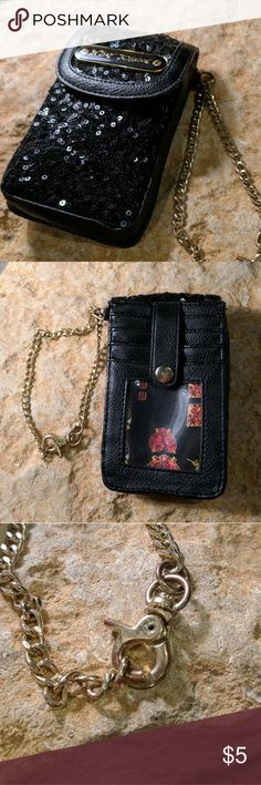 Betsey Johnson Black Sequin Wristlet Wallet Betsey Johnson Wristlet with black sequins and what seems like black leather although I can't authenticate. Holds a cell phone, drivers license and credit cards. Has a gold color chain with alligator clip. Seems to have lost it's last larger ring in the chain where is hooks to the other side or the chain was supposed to collect at the bottom of the alligator clip and the ring just needs to be pulled apart and put back together. Either way, it still…