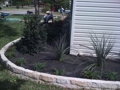 GroundScape, a Fort Worth Landscape Company, installs curved flowerbed edging out of austin stone.