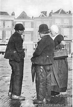 """Chatting on a Wet Street in Holland, 1906    In this picture a married couple is chatting with an old man on a rain soaked cobblestone street. The original caption for this photograph reads """"Conferentie over de dikte van de bieten."""" which Google translates as """"Conference over the thickness of the beat.""""   I am assuming that this is some sort of Dutch figure of speech for gossiping."""