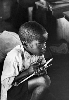 "Galería de fotos. ""Earnest boy squats on haunches and strains to follow lesson in heat of packed classroom"" (1960-1966) de Ernest Cole. Información sobre el autor en http://www.sahistory.org.za/people/ernest-cole #Apartheid"