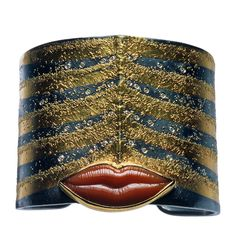 Very Man Ray.  This silver cuff features coral lips with 22 and 24 karat gold on and diamonds by Atelier Zobel.