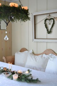 Gorgeous evergreen and crystal hanging candle holder, lovely white board walls, white linens, pretty details