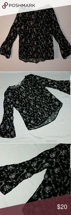 Available by Angela Fashions Peasant Top NWT!! This super cute black blouse has white floral print all over with 3/4 length bell sleeves. Excellent condition. Pleaded details in front. Lightweight.   19.5 inches across chest 14 inches from under arm to bottom seam  100% rayon. Available by Angela Fashion Tops Blouses