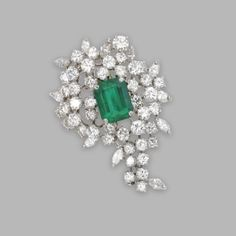 PLATINUM, EMERALD AND DIAMOND BROOCH Set in the center with an emerald-cut emerald weighing approximately 4.00 carats, framed by round and marquise-shaped diamonds weighing approximately 8.30 carats.