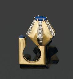 CARTIER, modèle créé par DINH VAN. Années 1960 RARE et EXCEPTIONNELLE BAGUE en forme de fleur stylisée soulignée de lignes de diamants brillantés sur la corolle côtelée et surmontée d'une plaque ronde de lapis-lazuli. L'anneau de forme carrée est ouvert et souligné d'un cabochon de lapis-lazuli. Monture en or jaune et gris 18 kts. Signée Cartier et Dinh Van. Hauteur totale: 4,5 cm. Tdd: 50.