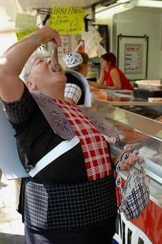 Woman in traditional dress eating raw herring the Dutch way.