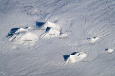 The snow-covered peaks of several volcanoes on the central Kamchatka Peninsula stand above a fairly uniform cloud deck that obscures the surrounding lowlands. In addition to the rippled cloud patterns—caused by interactions of air currents and the volcanoes—a steam and ash plume is visible extending north-northeast from the relatively low summit (2,882 meters above sea level) of Bezymianny volcano.