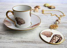 Collana artigianale realizzata con catenina color oro e pendente in porcellana dipinto a mano con decoro di conchiglie. La collana può essere abbinata ad una tazzina da caffè decorata con lo stesso tema decorativo.