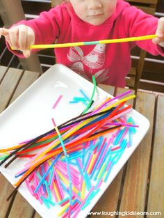 threading straw pieces on to long pipe cleaners for fine motor