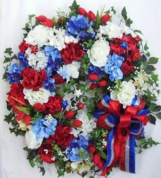 """This beautiful Patriotic July 4th door wreath sets on a nature grapevine wreath base.  The wreath is embellished with lots of Greenery, beautiful white Hydrangea, red/white Roses, red and blue Hydrangea The wreath is accented with three white/red/blue glitter stars. I finish the wreath with a red/white/blue glitter ribbon bow.   The wreath measures from tip to tip at 26"""" (L) x 25"""" (W) x 7.5""""(D)."""