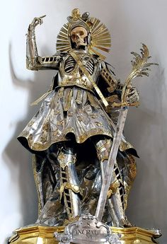 St. Pancratius. The Bones of St. Pancratius are found at the Church of St Niklaus in Wil, Switzerland. Taken from the Roman Catacombs, his bones were sent to St. Gallen in the 1670s, where a team of nuns dressed him in Roman-style costuming. In 1777 – the centenary of his bones arriving in Wil – he was re-dressed in this magnificent commissioned suit of armour.