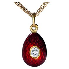 Fabergé gold and strawberry red guilloche enamel miniature egg pendant. The egg is set with an old cut diamond. The detachable gold mount is marked with workmaster's initials of August Hollming, and 56 zolotniks Imperial gold standard with Cyrillic initials ' YaL ' for St Petersburg assay master Yakov Liapunov. | 1stdibs.com