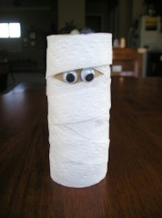 Use a small strip of bock construction paper then use torn strips of white construction paper to wrap around toilet paper tube, 2 googly eyes and you have a mummy