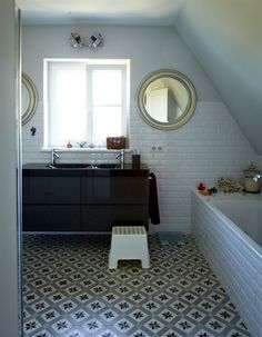 Floating vanity, mirrors flanking the window, sloped ceilings, patterned tile on the floor are a few of the reasons we love this bathroom.