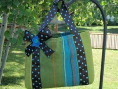 Dollar store place mat + dollar store spool of ribbon, a button & felt flower= cute hand bag/ tote.