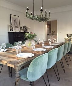 Delicious soft blue velvet on these dining chairs, perfect here with a wooden table and some green complements.