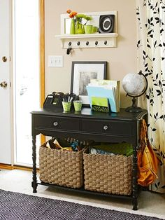 Small Space Storage Solutions: 1. Purchase a small console that fits on an entry wall, and remember a lower shelf is an added bonus!  Use the top as a desk and baskets below for a centralized solution designed to hold everyday necessities for grab and go convenience.    --  love the black console and the silhouette curtains