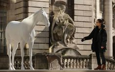 Flint the Whippet and owner Dolly Feaver stand beside the new sculpture 'The White Horse' by Artist Mark Wallinger after it was unveiled outside the headquarters of The British Council on the Mall in London