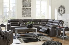 """Information: Ultra cool, ultra-contemporary, and ultra-comfortable, this sectional sports a fabulous faux leather enhanced with jumbo stitching for fashion-forward flair. """"Divided"""" cushion design on the back and footrest is indulgent yet anything but bulky. Scooped sides give the pillow top armrests that much more allure. Features: Part of Kincord Collection from Ashley Frame constructions have been rigorously tested to simulate the home and transportation environments for improved durability Mi"""
