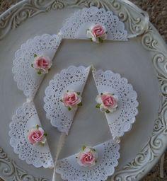 Un conjunto de seis pequeños tapetes han sido ensartados para hacer un banner tan tan dulce. Cada sección ha sido adornado con una rosa en dos tonos