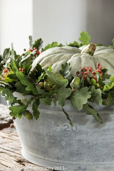 Autumn pumpkin decoration galvanized tub - wreath of oak leaves, berries, acorns and chestnuts.