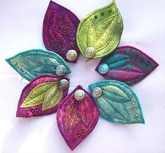 Imagine making concrete leaves, wiring together to form a  wreath & painting in bright colors like this felt example.