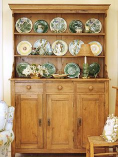 Plate Scene in Green: Green relates each of these plates to the others, but it is the woodland theme that underscores the theme of the display. Perfectly housed in a vintage pine hutch, the arrangement is accented with small creamers and a lamp.