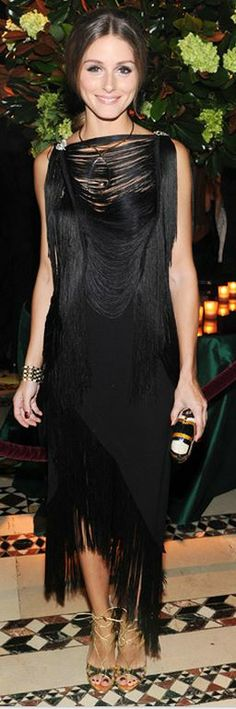 Who made  Olivia Palermo's black fringe dress, brown print clutch handbag, and gold lace up sandals that she wore in New York?